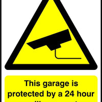 This garage is protected by a 24 hour surveillance system sign