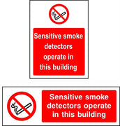 Sensitive smoke detectors operate in this building sign
