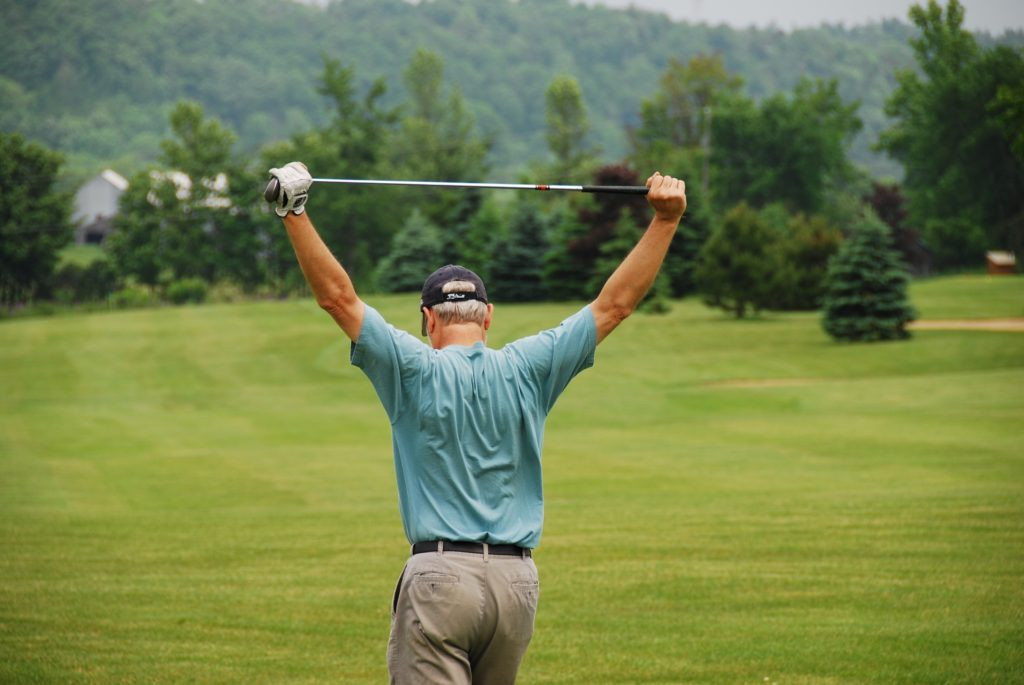 A golfer shows his frustration or he could be just working out some tight muscles.