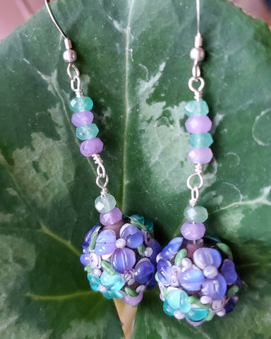 Long Lavender Flower Garden Earrings, Sold Sterling Silver, Large round Floral Lampwork Glass beads with lavender purple and turquoise blue flowers, they dangle below a long stream of blue and lavender Quarts Stone. Sold Sterling Silver