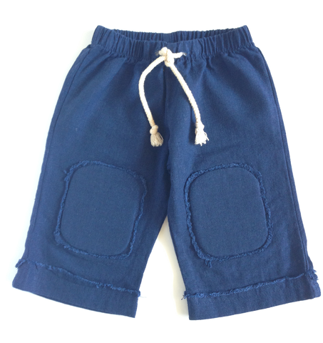 Your little man will love to explore in these cool & casual cruise-wear pants. Organic, soft cotton linen pant with elastic waist and decorative nautical cord ties. Frayed edges on cuffed hem and padded knee patches to protect those tender knees.