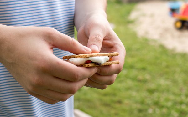 Hands hold a perfectly cooked smore. Pear and Simple in Port Washington, Wisconsin share amazing campfire recipes.