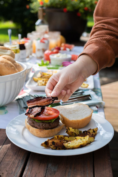 Adding a slice of bacon to BBQ Bacon Blue Cheese Burger. Get more ultimate backyard bbq recipes and gifts from Pear & Simple in Port Washington, Wisconsin.