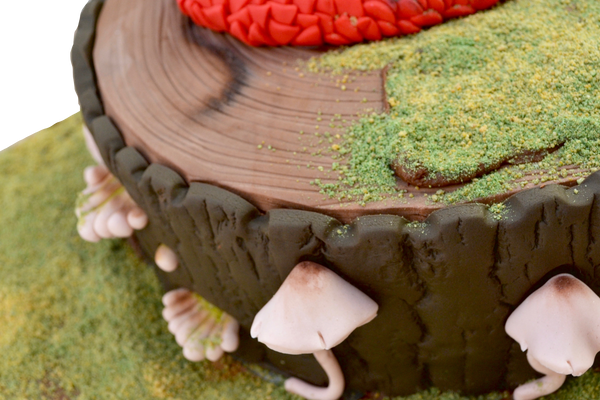 red dragon cake sitting on a edible fondant tree stump and edible fondant mushrooms with edible grass by sugar street boutique toronto.