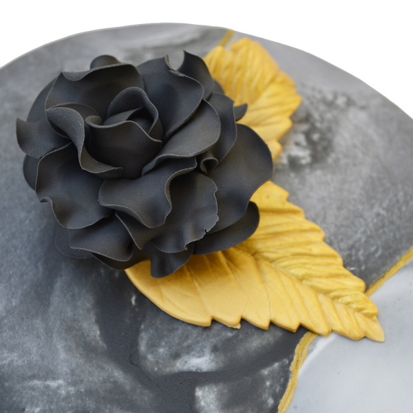 Black marble lemon cake with gold accents and an edible black rose, filled with lemon curd and a light lemon icing in between layers. Sugar Street Boutique toronto cakes.