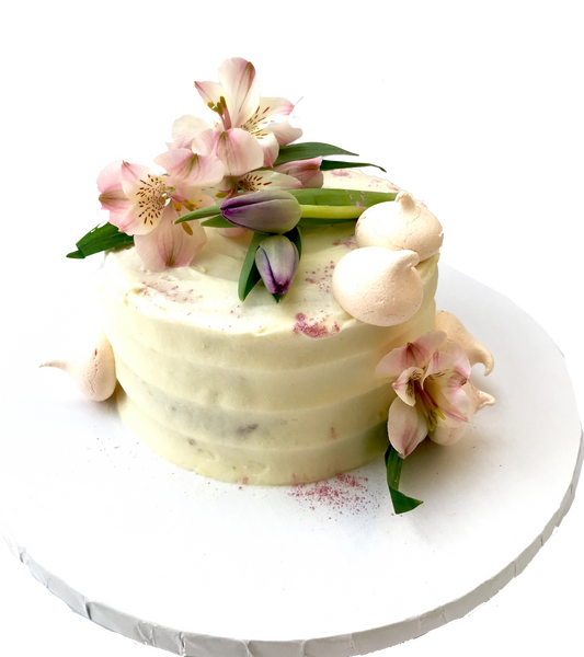 4 layer lemon cake with lemon curd in between layers and iced with a light lemon icing. Decorated with meringues, lillies & tulips by sugar street boutique toronto.