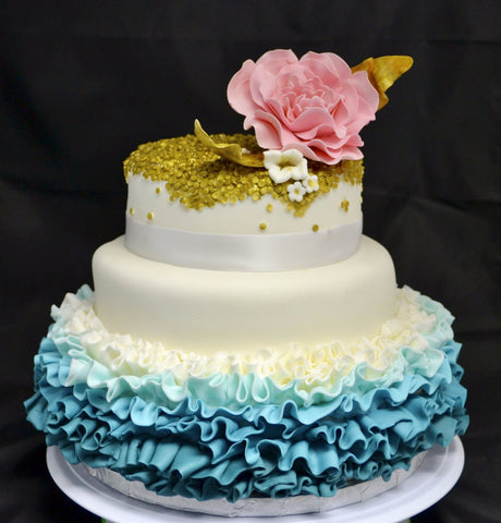 3 TIER WEDDING CAKE WITH BLUE OMBRE RUFFLES AND GOLD SEQUIN WITH A PINK FLOWER ON TOP BY SUGAR STREET BOUTIQUE TORONTO.