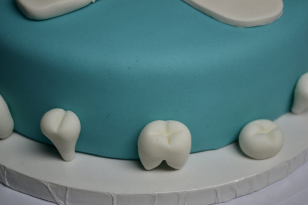 chocolate cake covered with fondant decorated with an edible dental probe, edible dental mirror, edible denture, edible dental floss and edible teeth by Sugar Street Boutique Toronto