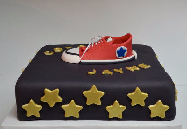 Nestle red show award cake with gold edible stars and a red converse fondant shoe over a black fondant covered cake by Sugar Street Boutique Toronto