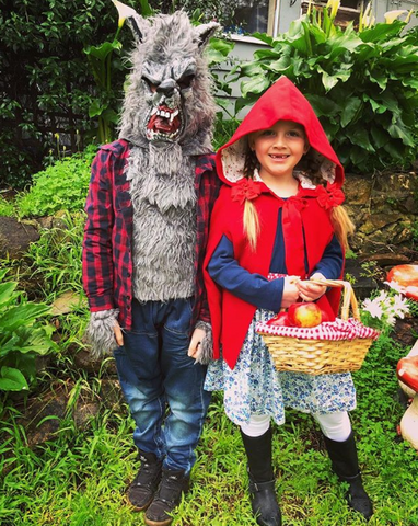 Girl in a red riding hood costume and big bad wolf