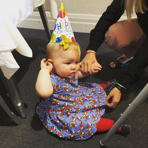 Baby girl wearing a blue and red birthday dress and a happy birthday hat