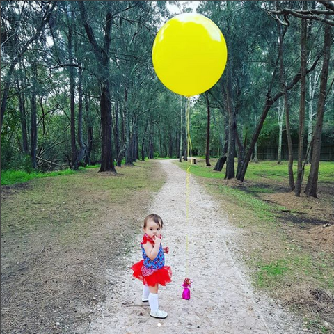 A baby girl wearing a blue dress with a red tulle skirt and flutter sleeves standing beside a bottle with a yellow balloon tied on it