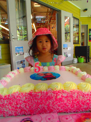 A girl wearing an ice cream print dress and polka dot hat with a pink cake in front of her