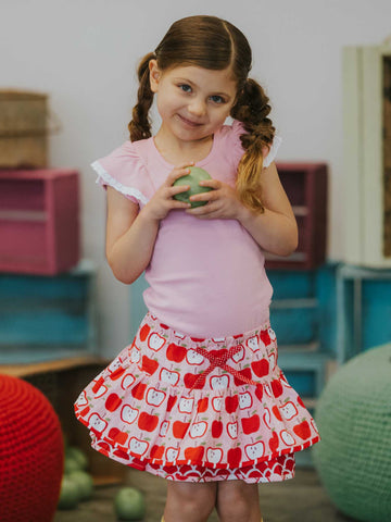 Girl in a pink tee and pink apple skirt