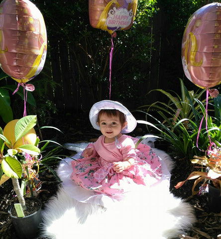 A baby girl sitting on a faux fur cushion wearing a pink floral dress and hat with three balloons around her