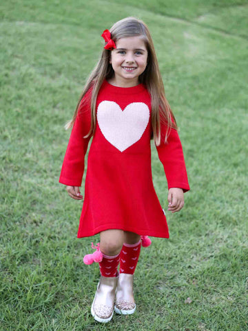 Smiling girl in a knitted red heart dress