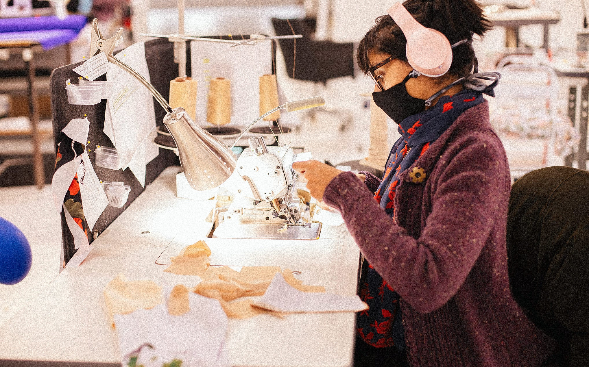 A sewist sits profile to the camera wearing a face mask, glasses and pink headphones as she sews.