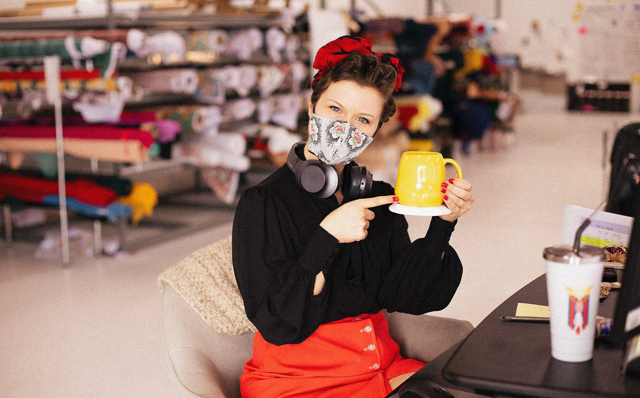 A woman wearing a face mask & a bandana on her head sits in a chair and poses pointing to a yellow mug.