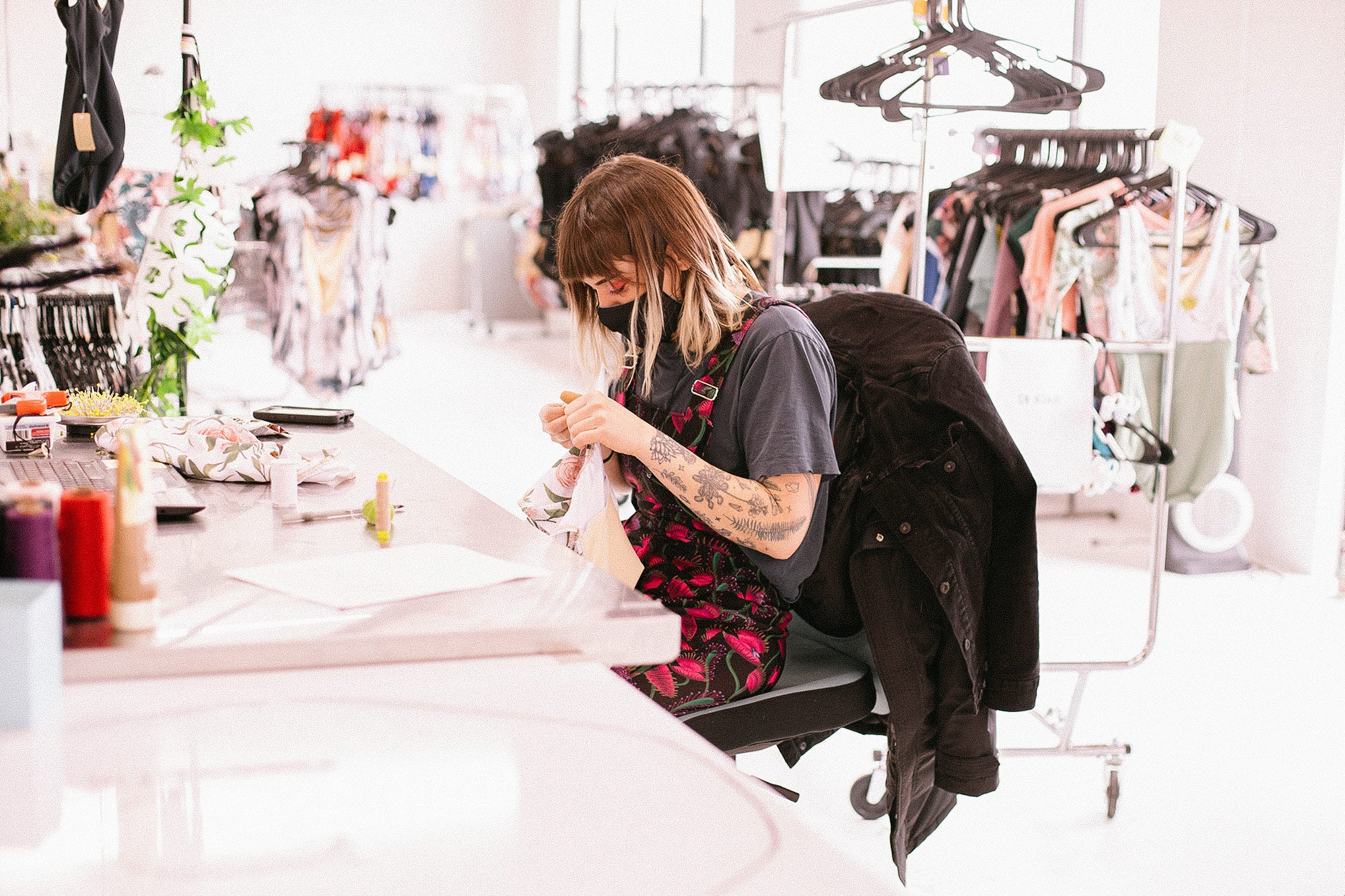 A woman with brown hair wearing colorful black & pink floral overalls sits at a table and inspects a leotard.