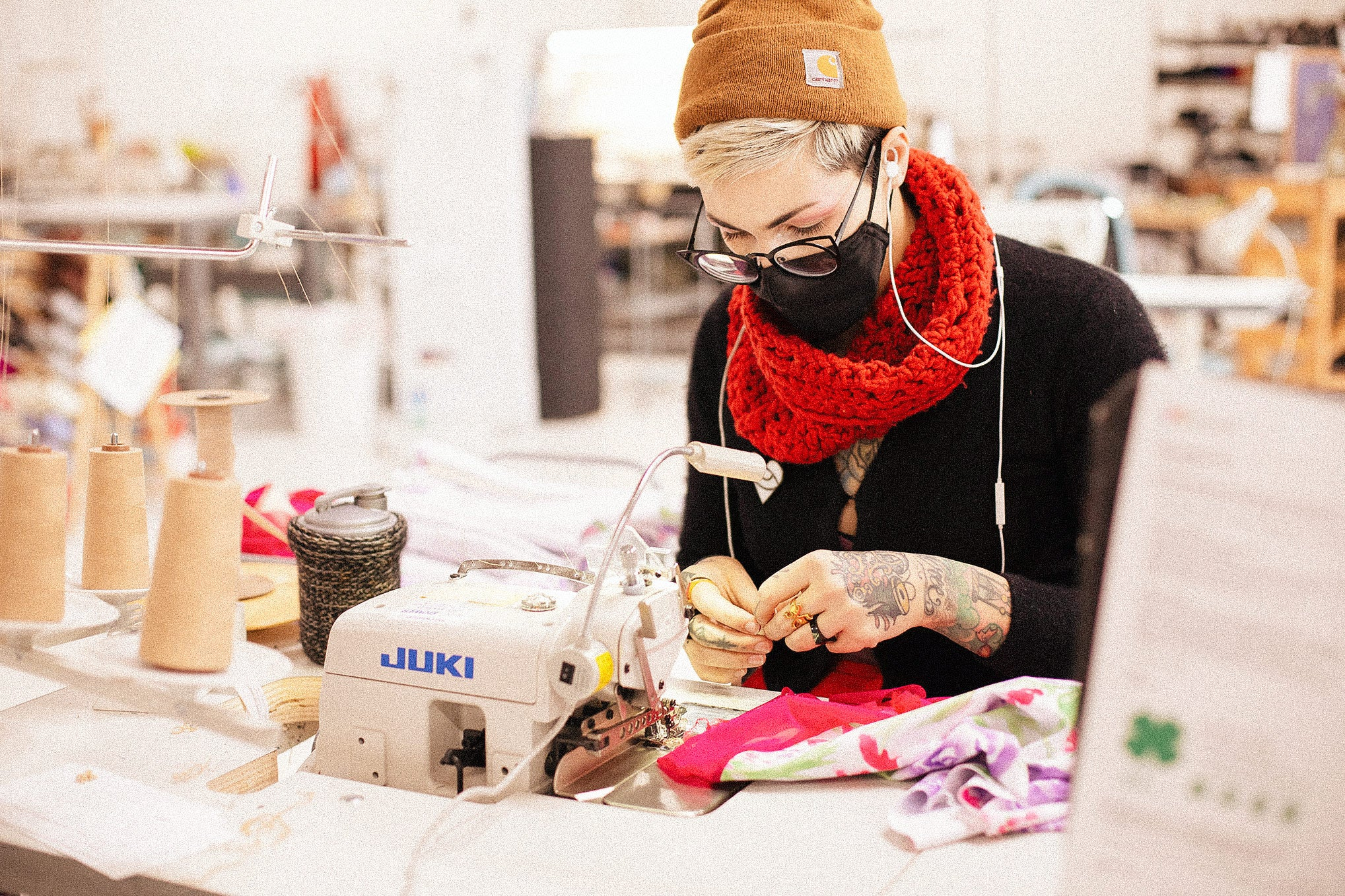 A sewist wearing a face mask, glasses and a red scarf sits at her sewing machine with fabric in her hands.
