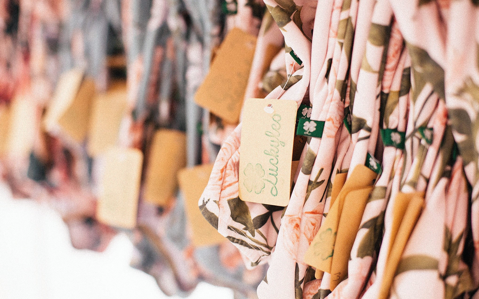 A close-up shot of racks of colorful leotards hanging together with a brown Luckyleo hang tag in focus.