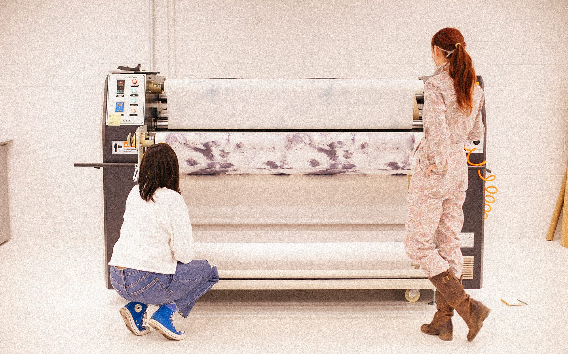 Two women are in front of a large fabric printed. The woman on the left is wearing blue sneakers and kneeling while the woman on the right wears tall boots and stands with her foot kicked back and a hand in her pocket.