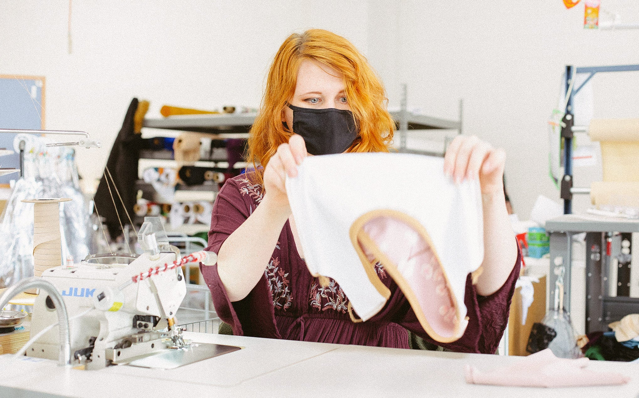 Taylor sits at a sewing machine and is looking at a leotard she is holding up in front of her.