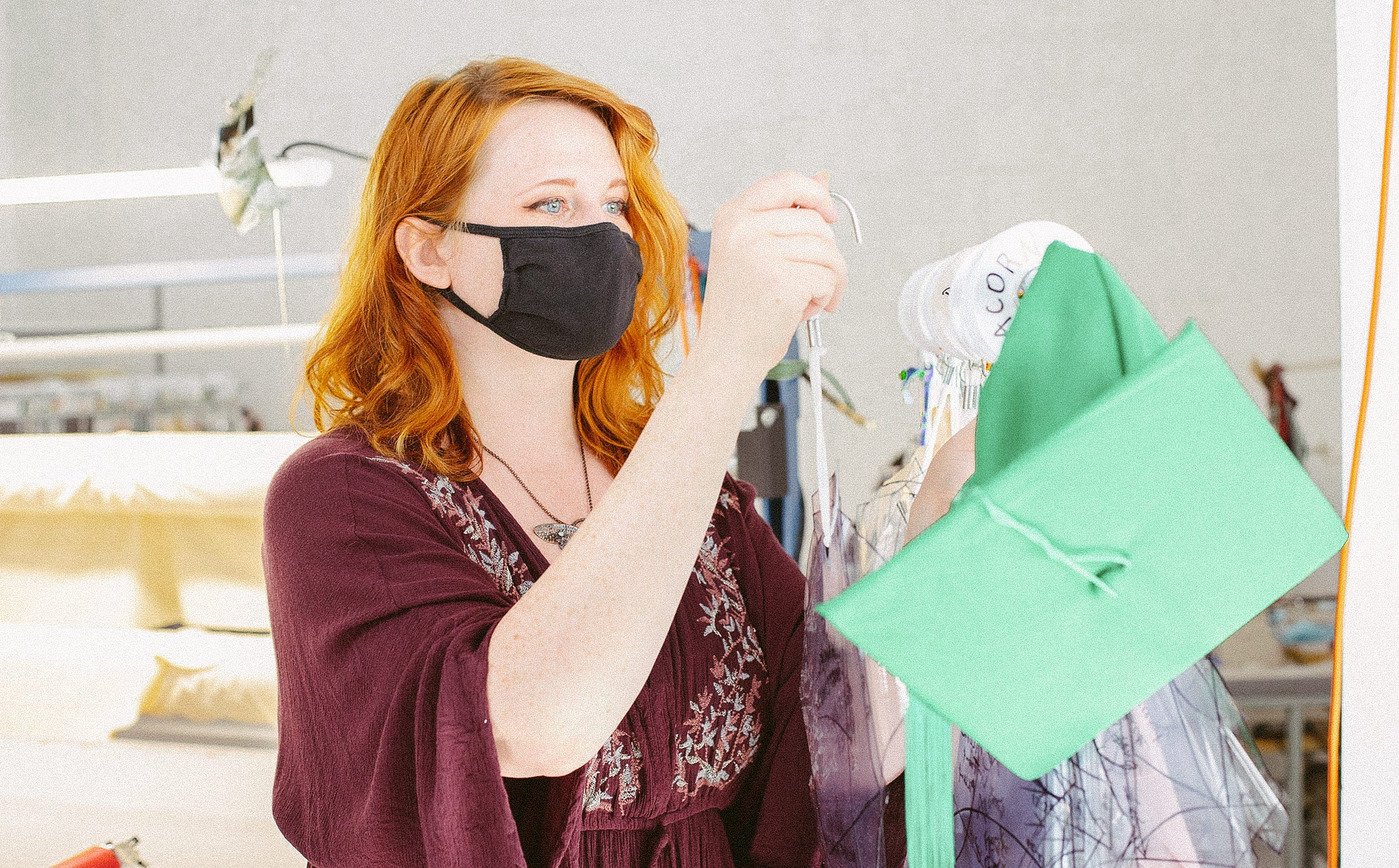 Taylor pulls a pattern from a rack with a green graduation cap hanging on the end of the rack.