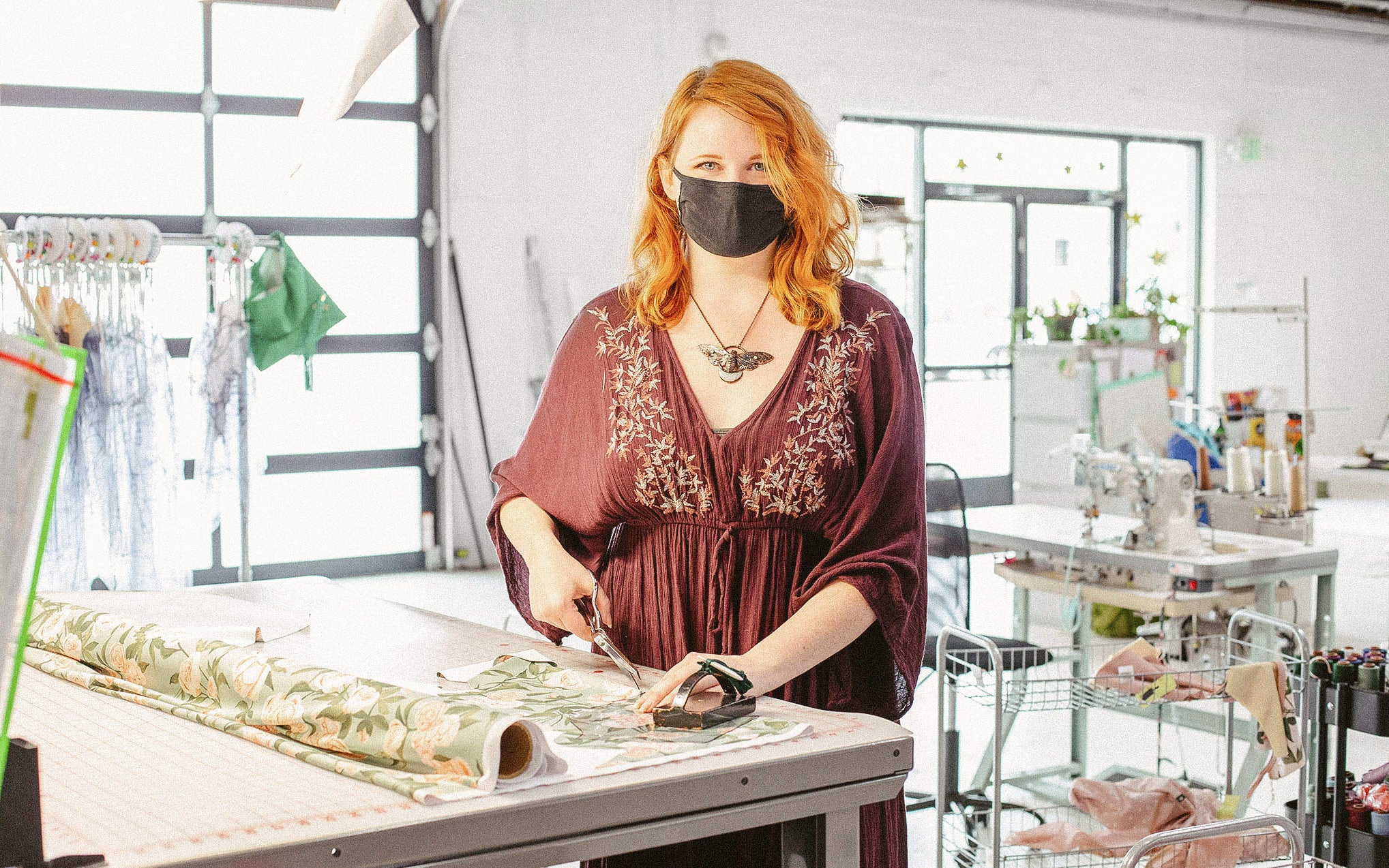Taylor stands at a cutting table with scissors in her hand and a roll of fabric next to her.