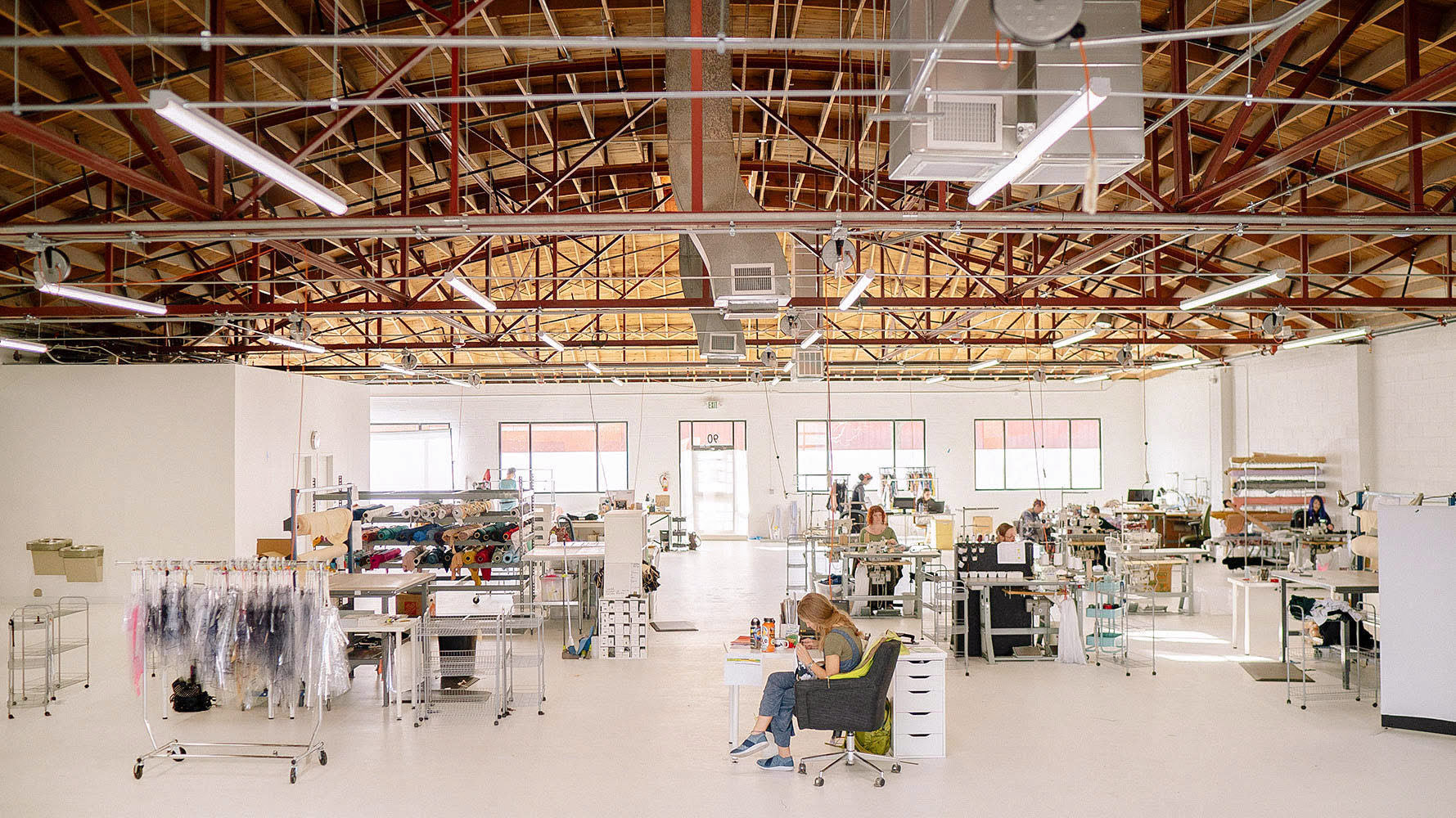 Large workshop space with white walls & floors and a vaulted wooden ceiling. The room is filled with racks of fabric, cutting tables, and industrial sewing machines.