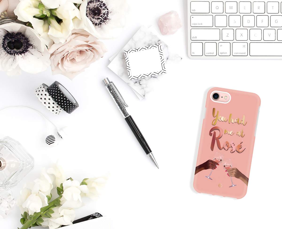 "flatlay of desk and pink shockproof iPhone case with design of two hands clinking rosé glasses and text that states ""you had me at rosé"""
