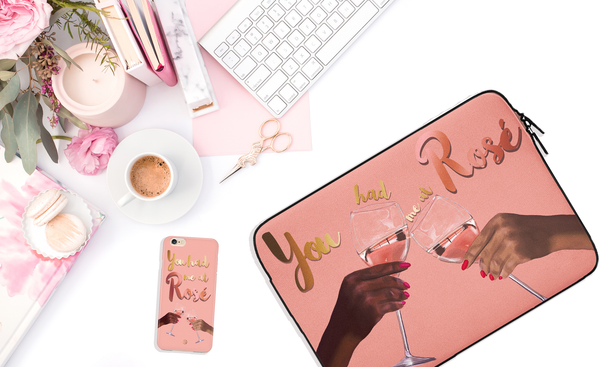 "flatlay of matching Pink laptop case and iPhone case with hands holding glasses clinking Rosé wine glasses and designs states ""you had me at rosé"""