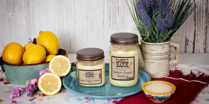Lemon Sugar Cookie mason jar candles sitting in between a small, metal tub filled with lemons and a small, ceramic dish of raw sugar