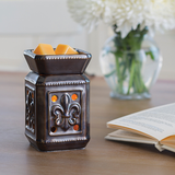 The Fleur de Lis wax melt warmer sits on a table beside an open book with a bouquet of white flowers in the background