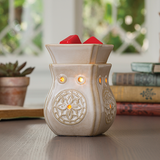 The Insignia Midsize Illumination wax melt warmer sits on a table in front of a small stack of books and a small potted plant