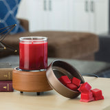 The Pewter Walnut wax melt warmer sits disassembled on a counter with a 10 oz candle on its warming plate and wax melts in its top dish