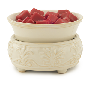 2-in-1 wax melt warmer in a creamy, sandstone color with fleur de lis and palmette designs around the base