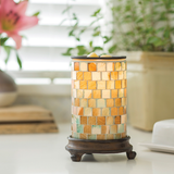 The Mosaic Sea Glass wax melt warmer sits on a table with a green potted plant and a large, pink flower sitting in the background