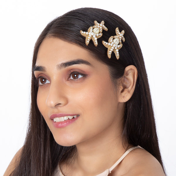 model wearing handmade gold shell beaded bobby pin set