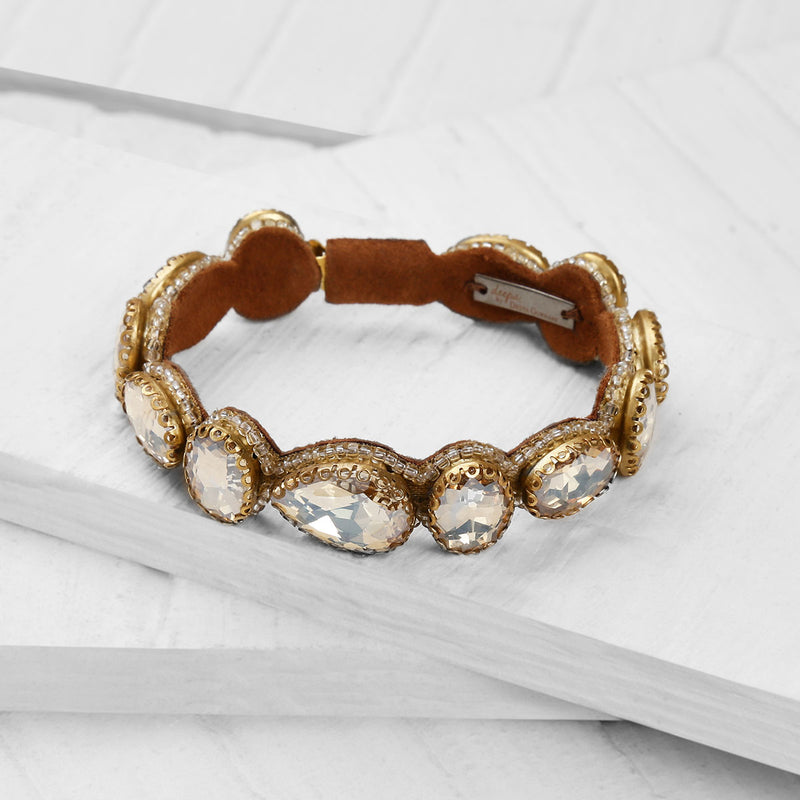 Deepa by Deepa Gurnani Handmade Embroidered Jordyn Bracelet in Gold on Wood Background