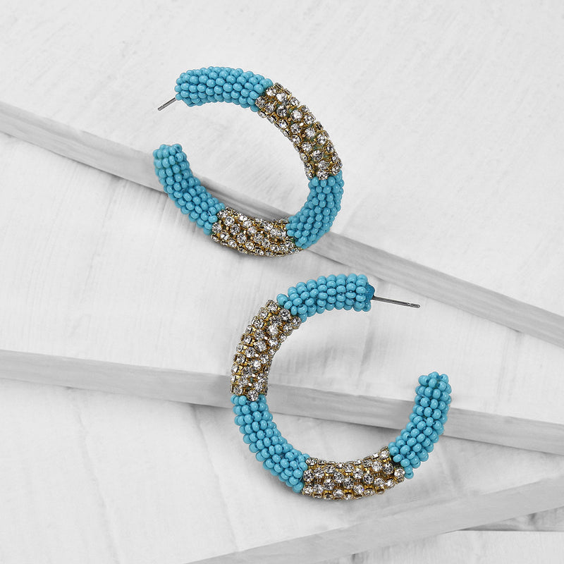 Deepa by Deepa Gurnani Handmade Beaded Hoop Earrings in Aqua on Wood Background