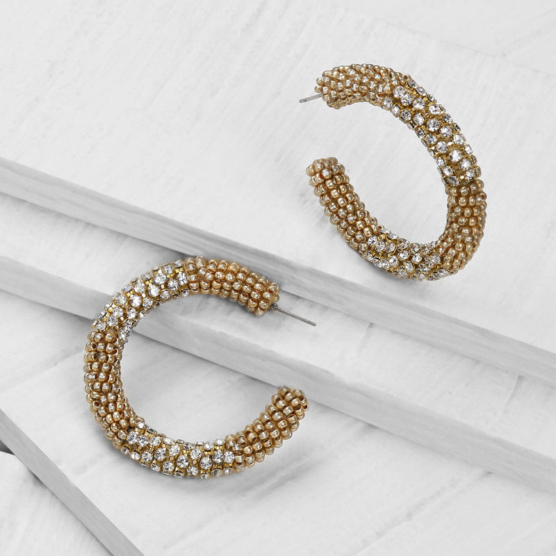 Deepa by Deepa Gurnani Handmade Lana Hoop Earrings Gold on Wood Background