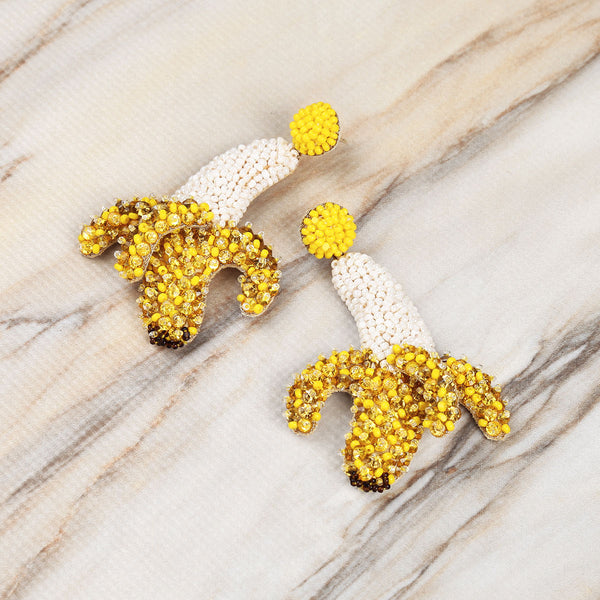 Deepa Gurnani Luxe Handmade Embroidered Banana Earrings on Marble Background