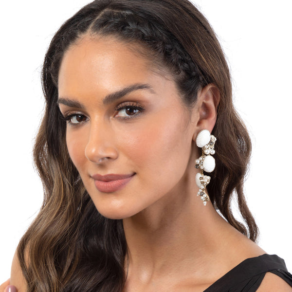 Model wearing shell earrings with pearl accents