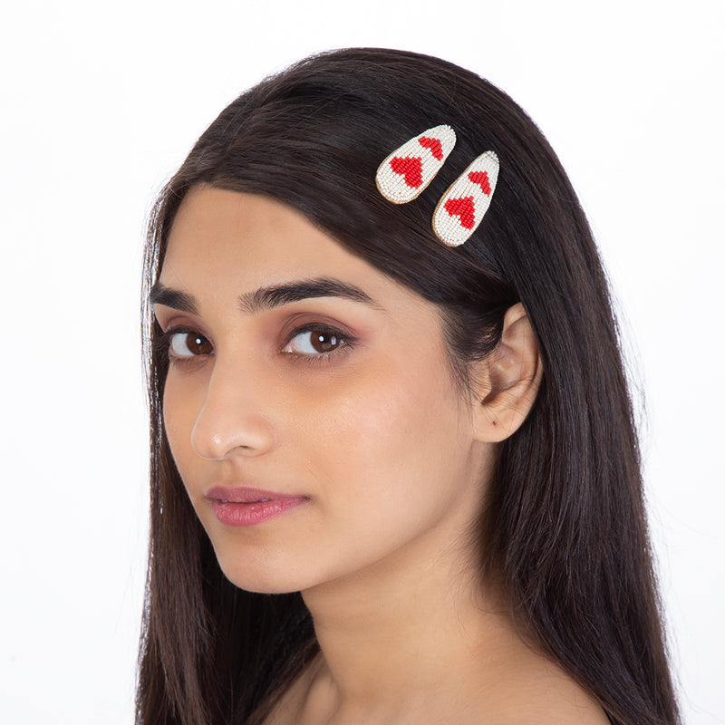 Model wearing handmade beaded red heart clip set