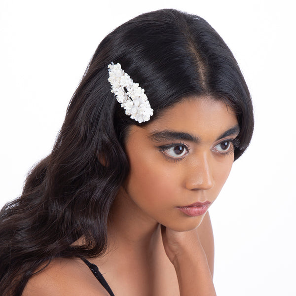 Model wearing handmade ivory beaded flower hair clip
