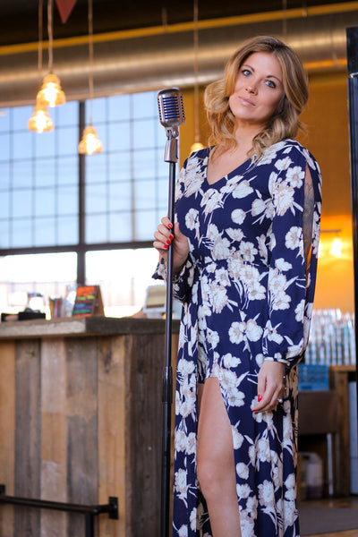 Woodstock, Virginia Woodstock Brewhouse The Gypsy Catwalk photo shoot 2017. This stunning floral romper is made for sweet spring afternoons and vibrant summer nights! Featuring a gorgeous floral print in navy, it's such a bold look for any day! The material is lightweight and slightly textured, while the wrap style at the bodice and v-cutouts in front and sleeves add the perfect pop of style! This romper also features a shorts and a zipper in back! From vacation days to the vineyards for brunch, as you can