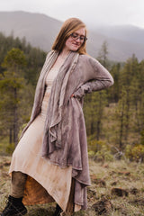 Sinew Moon employee wearing a dress and cardigan with her hand on her hip standing in a pine tree forest