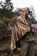 A man standing in front of a bush, holding a velour fabric across his back