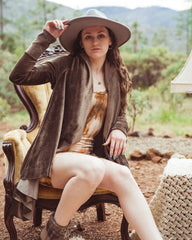 Sinew Moon seamstress sitting on a gold velvet chair with a leotard, velvet cardigan and brimmed hat